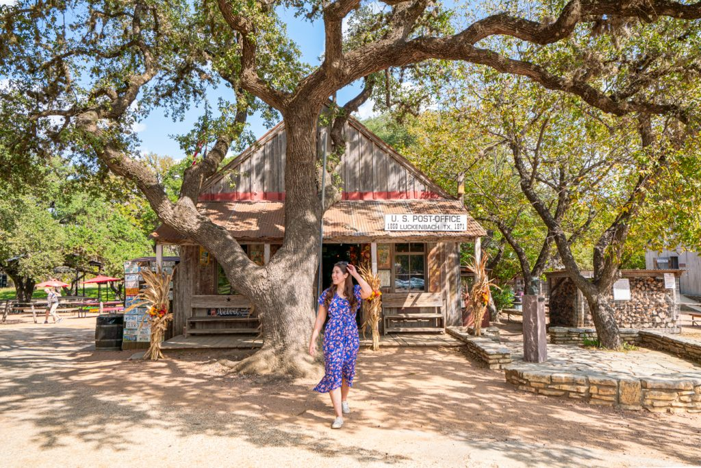 kate storm in a blue dress in front of the luckenbach post office