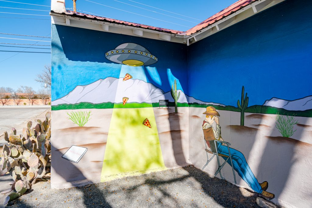 mural showing pizza slices being taken by a ufo in marfa texas