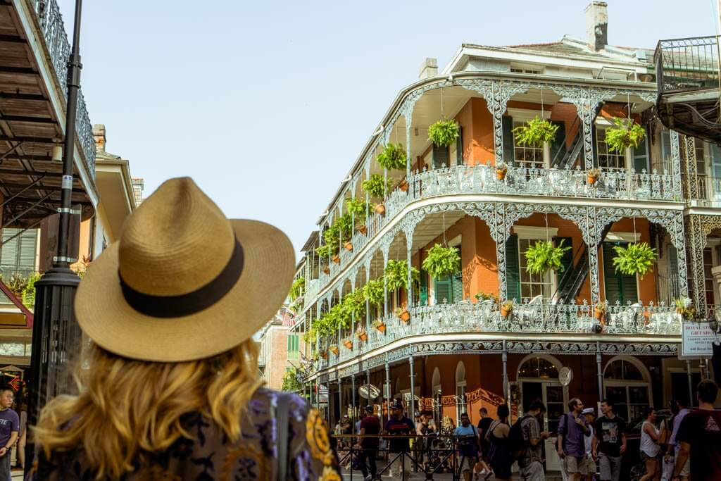 Blonde woman in a straw hat looking at a beautiful brick building in NOLA Garden District, one of the best weekend getaways in the south