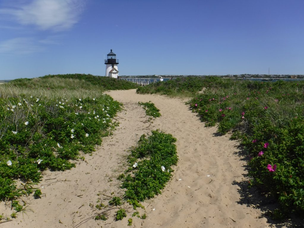 sandy path leading to a lighthouse in nantucket, one of the most romantic us honeymoon ideas