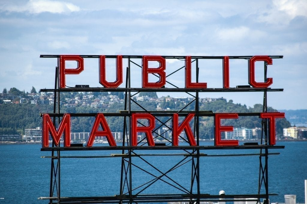 Seattle Public Market red sign with ocean visible in the background. Pike Place Market is an essential stop when stepping 3 days in Seattle Washington!