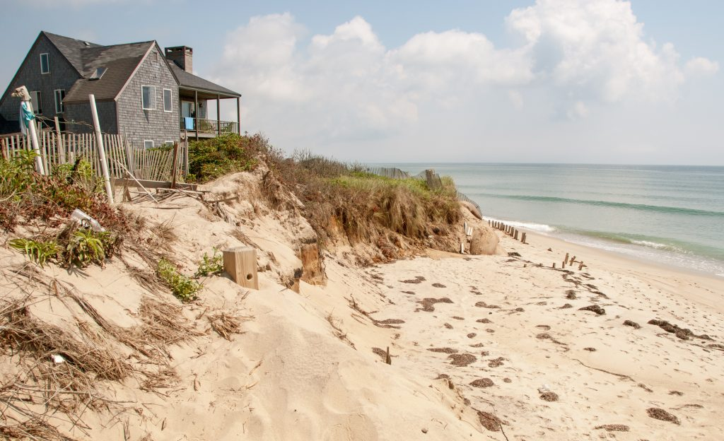 wooden beach house on the coast of marthas vineyard, one of the great honeymoon places in usa, with sand and water to the right of the photo