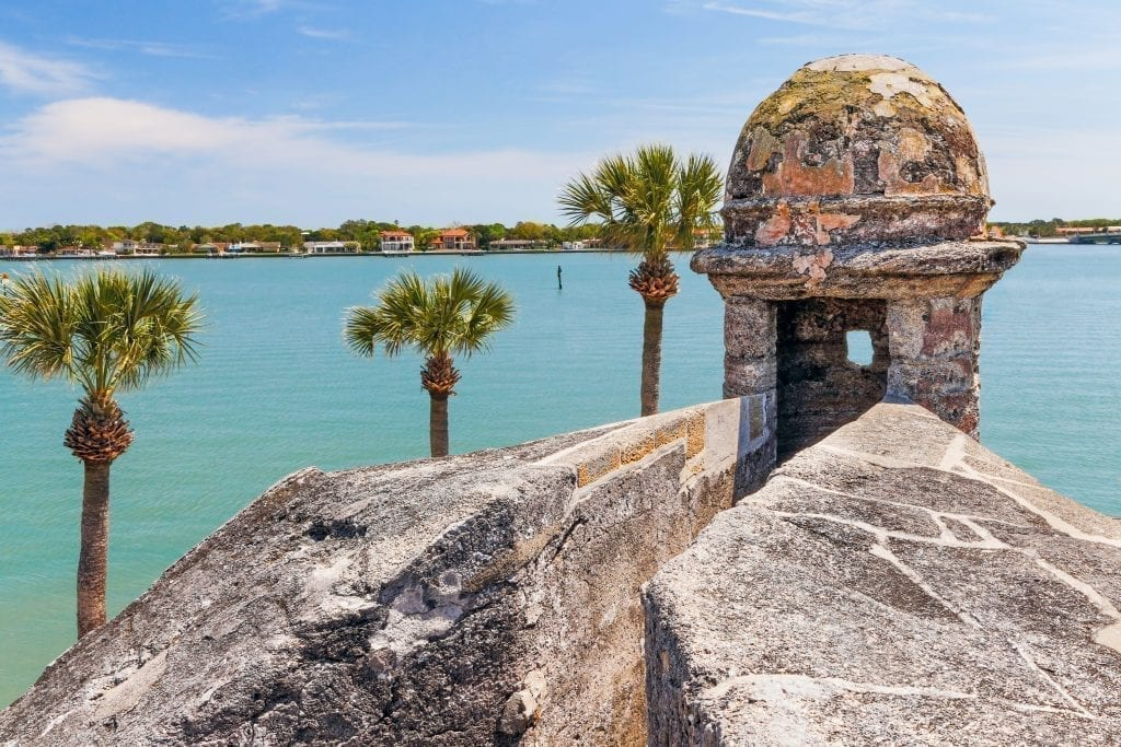 View of palm trees and ocean water over the stone wall of St Augustine Florida's 17th century fort. St Augustine is one of the best weekend trips in the south