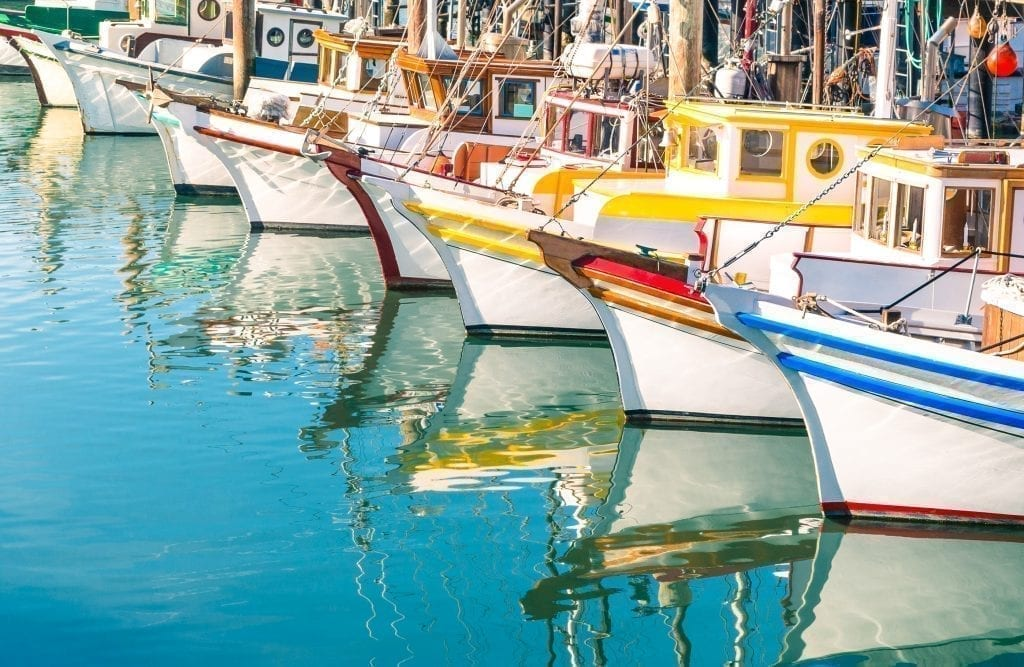 Colorful boats reflecting in the water at Fisherman's Wharf in San Francisco CA