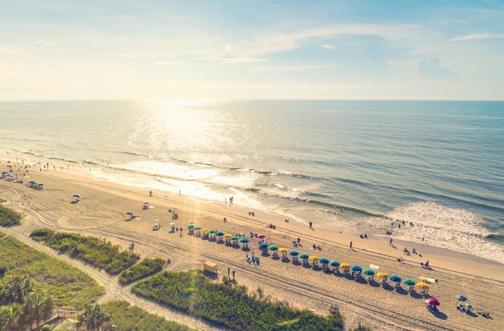 Myrtle Beach South Carolina as seen from above at sunset, with colorful umbrellas lining the beach