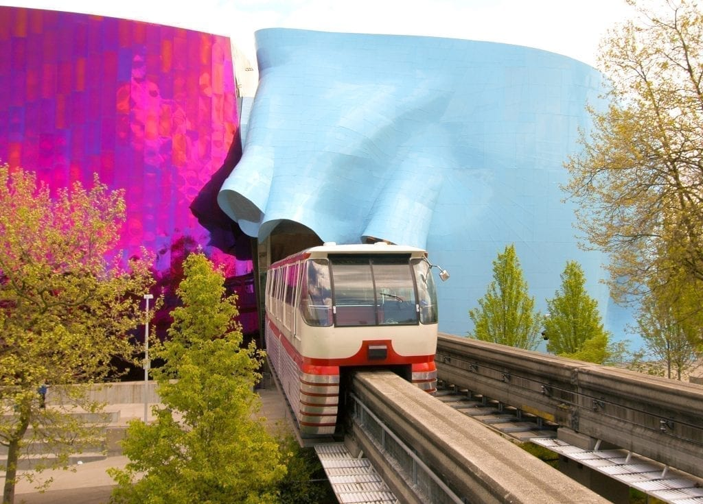 Seattle Monorail leaving a colorful tunnel, with purple on one side of the tunnel and blue on the other