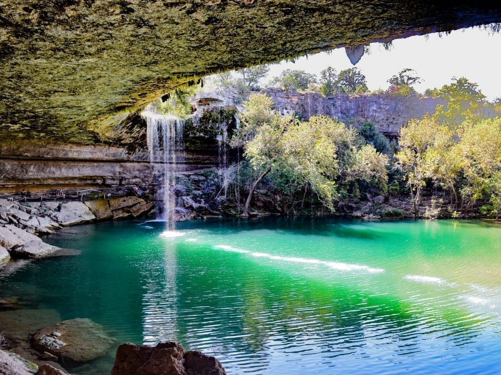 Hamilton Pool Preserve in Dripping Springs Texas with waterfall visible on the left side of the photo
