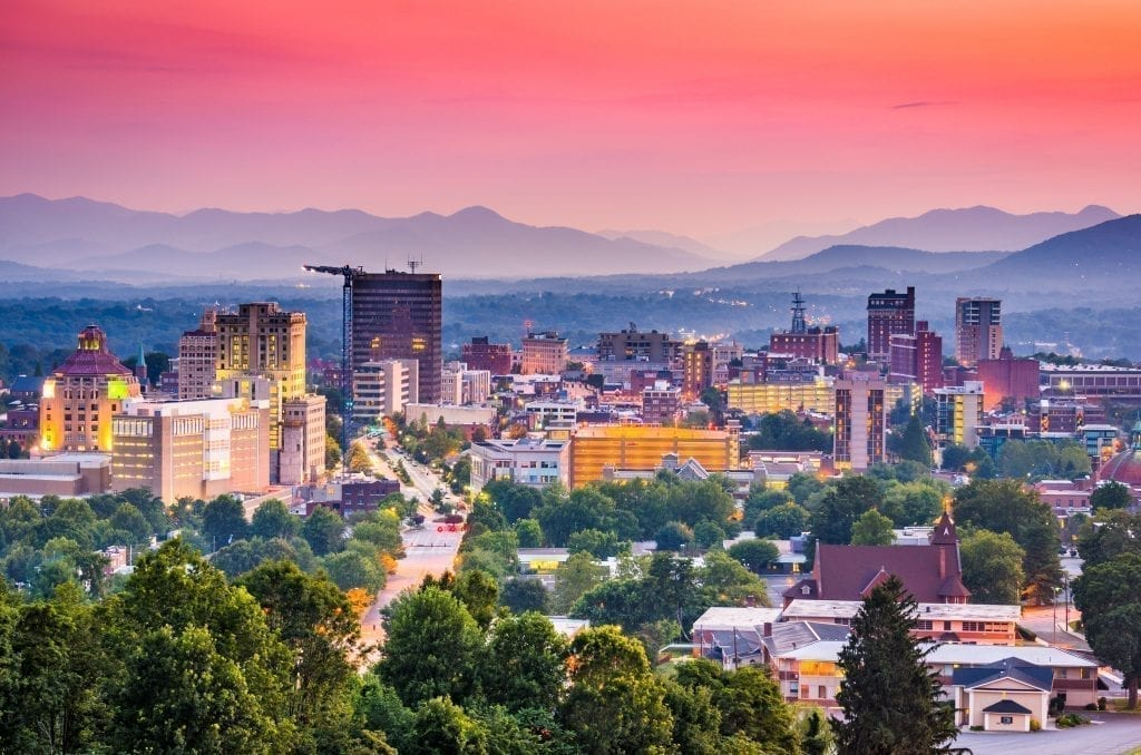 Skyline of Asheville NC at sunset with Blue Ridge Mountains in the background, one of the best weekend trips in the south