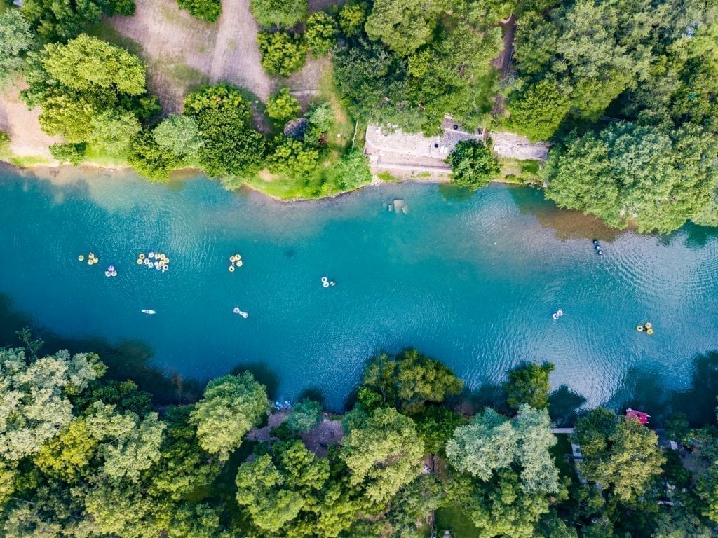 Drone photo from above of a Texas river with people floating in intertubes down it