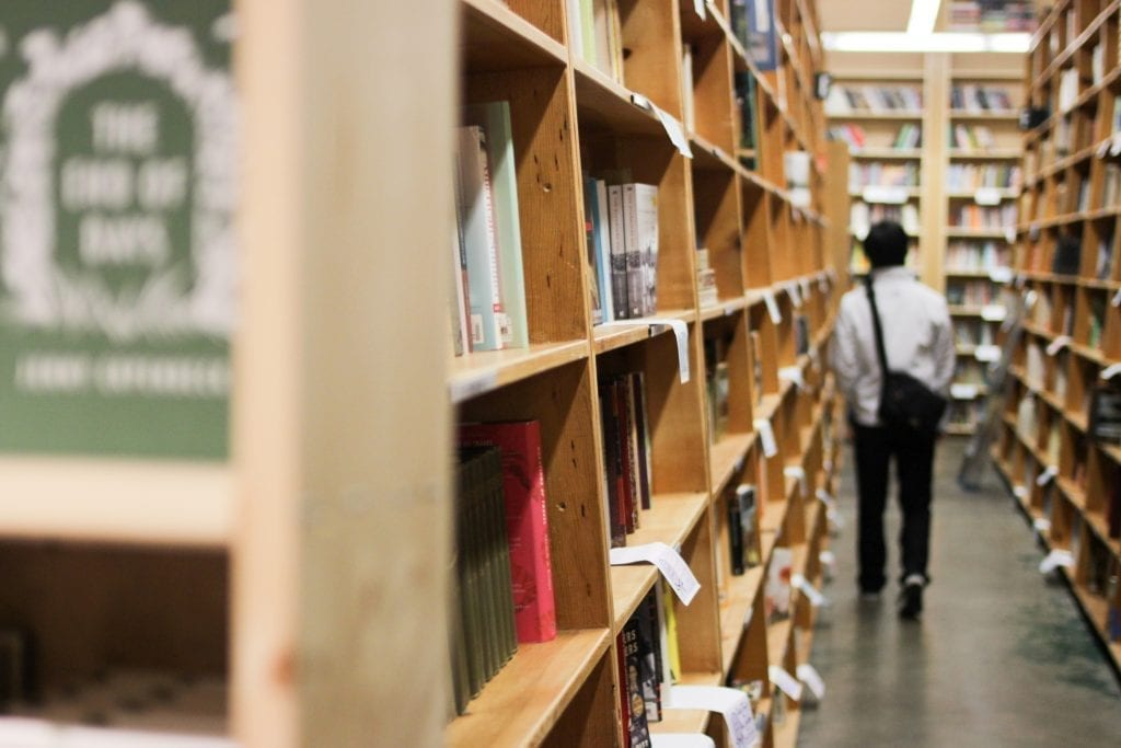 Photo of a man walking away from the camera down an aisle of bookshelves in Powell's City of Books, one of the first stops on this 3 day in Portland weekend getaway itinerary