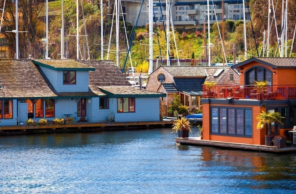 Houseboats on the water in Seattle WA with sailboats visible behind them--a beautiful sight you'll experience many times during this 3 day Seattle itinerary