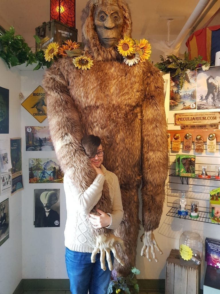 The author of this Portland blog post holding onto a sasquatch statue at the portland peculiarium