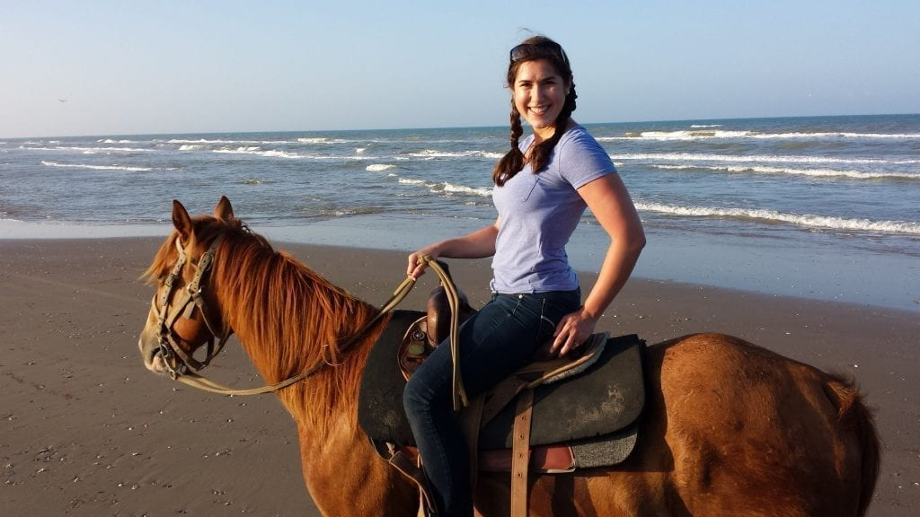 Kate Storm riding a horse on the beach on South Padre Island Texas