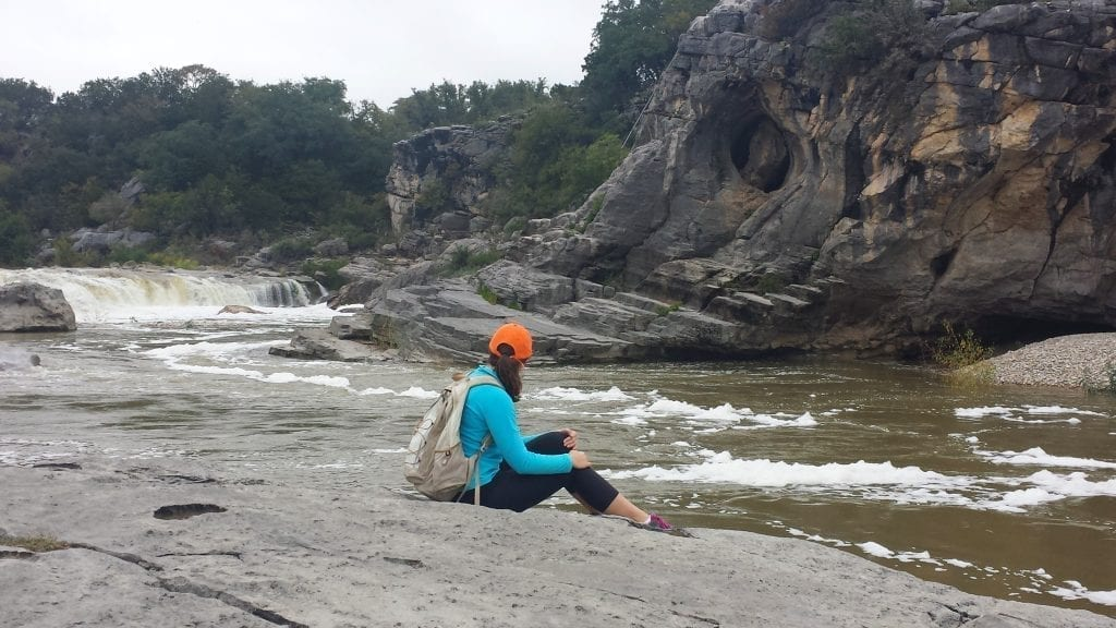 Kate Storm wearing a backpack and sitting on the edge of Pedernales Falls on a cloudy day. Pedernales Falls is one of the best day trips from San Antonio Texas