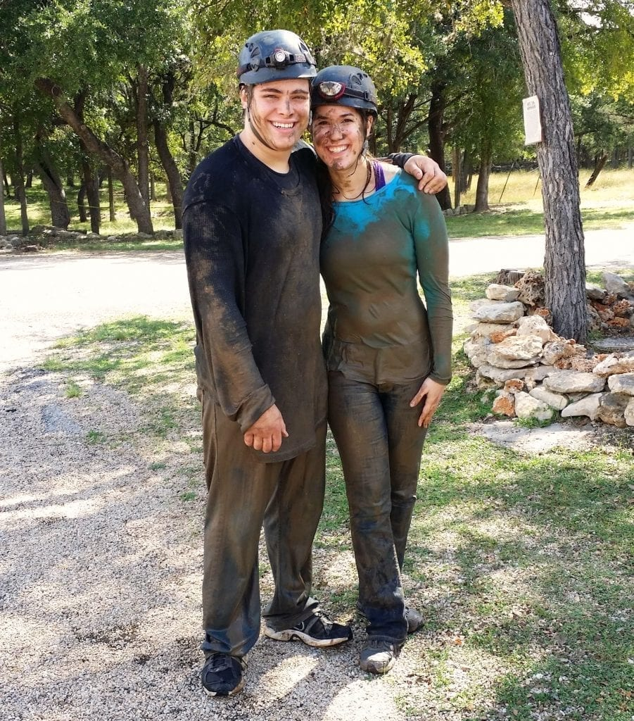 Kate Storm and Jeremy Storm covered in mud after touring Cascade Caverns on a day trip from San Antonio TX