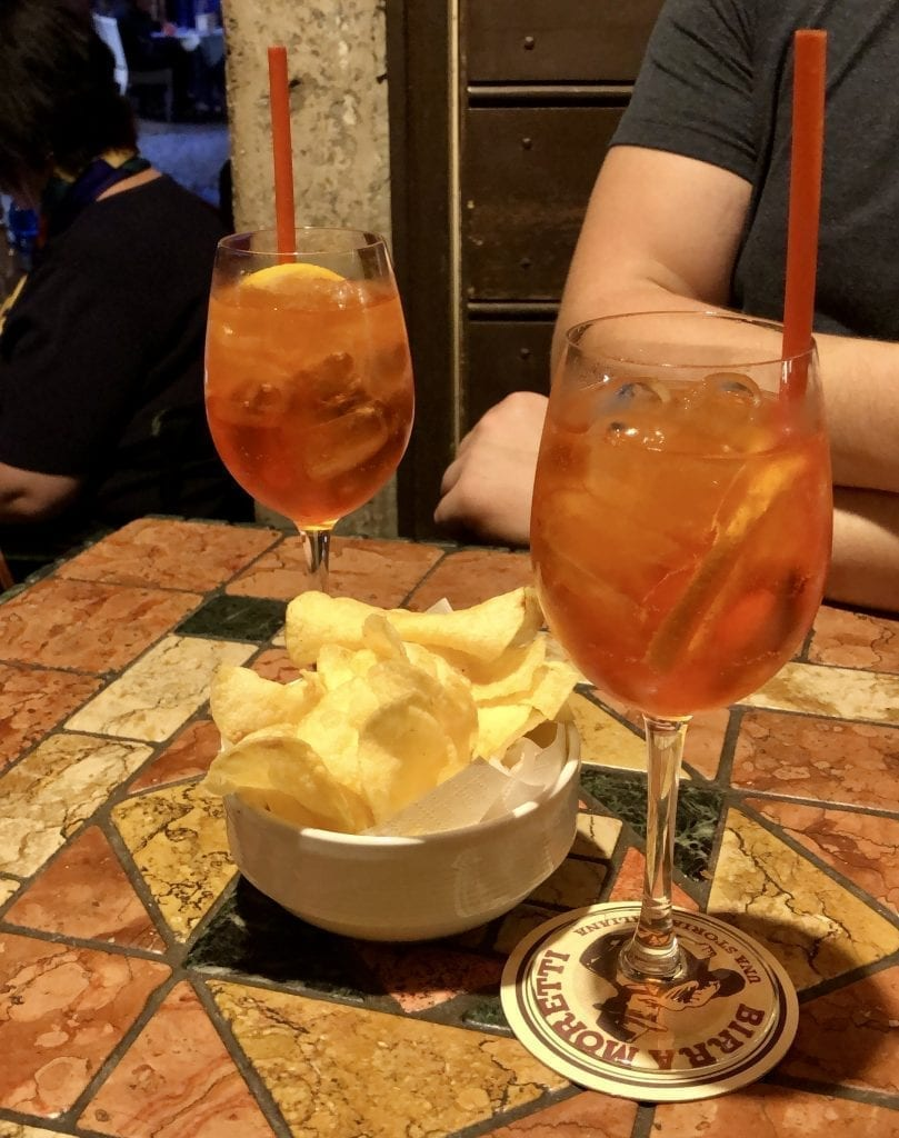 2 aperol spritzes on a small table in Rome at night with a small bowl of potato chips between them