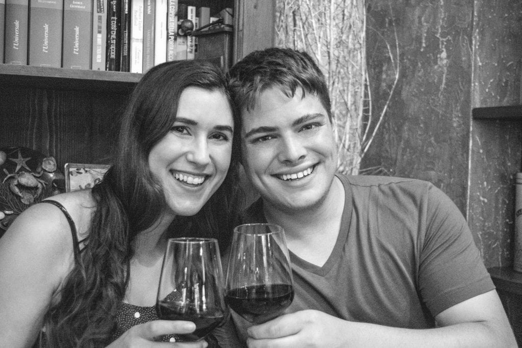 Kate Storm and Jeremy Storm holding up wine glasses in a restaurant in Florence at night. The photo is black and white.