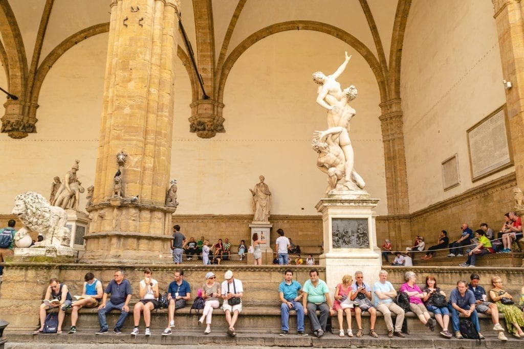 Tourists sitting in front of statues displayed in Piazza Signoria, as seen as part of a Florence itinerary