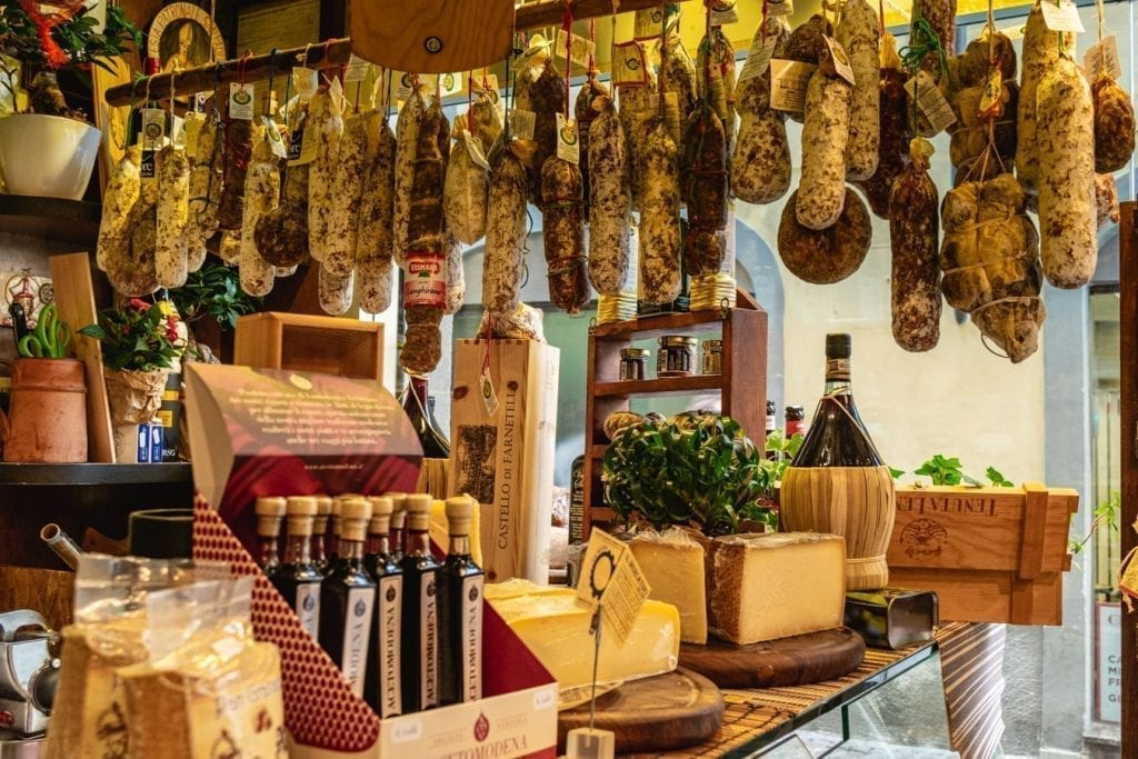 sausages hanging in a small shop in florence, how to save for a trip includes eating at home more