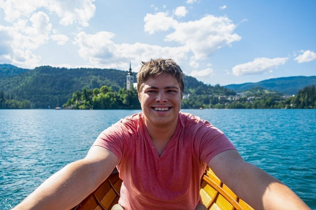 Jeremy Storm rowing a small wooden boat in Lake Bled, wearing a melon colored shirt