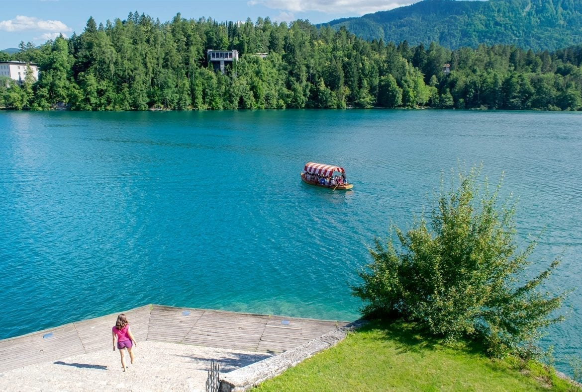 Kate Storm in a pink shirt descending a staircase on Bled Island with the lake visible in the background