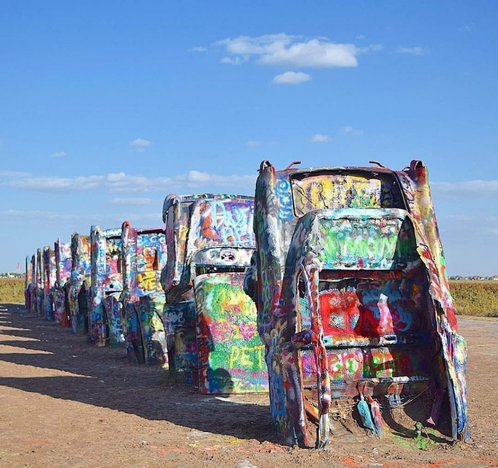 10 spray-painted cadillacs with their front ends buried in the sand at Cadillac Ranch outside of Amarillo Texas--with odd sights like this it's no surprise there are so many Texas quotes out there!