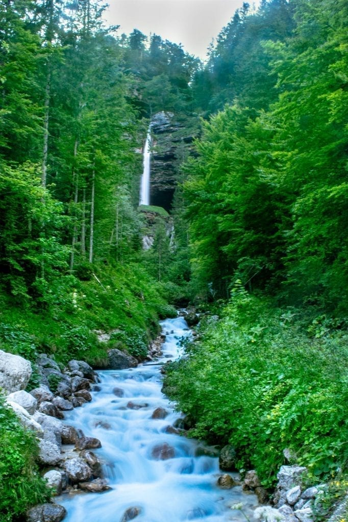 Pericnik Falls in Slovenia with flowing Soca River in the foreground