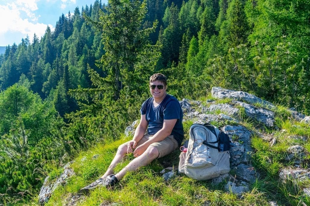 Jeremy Storm sitting on a forested trail in Slovenia
