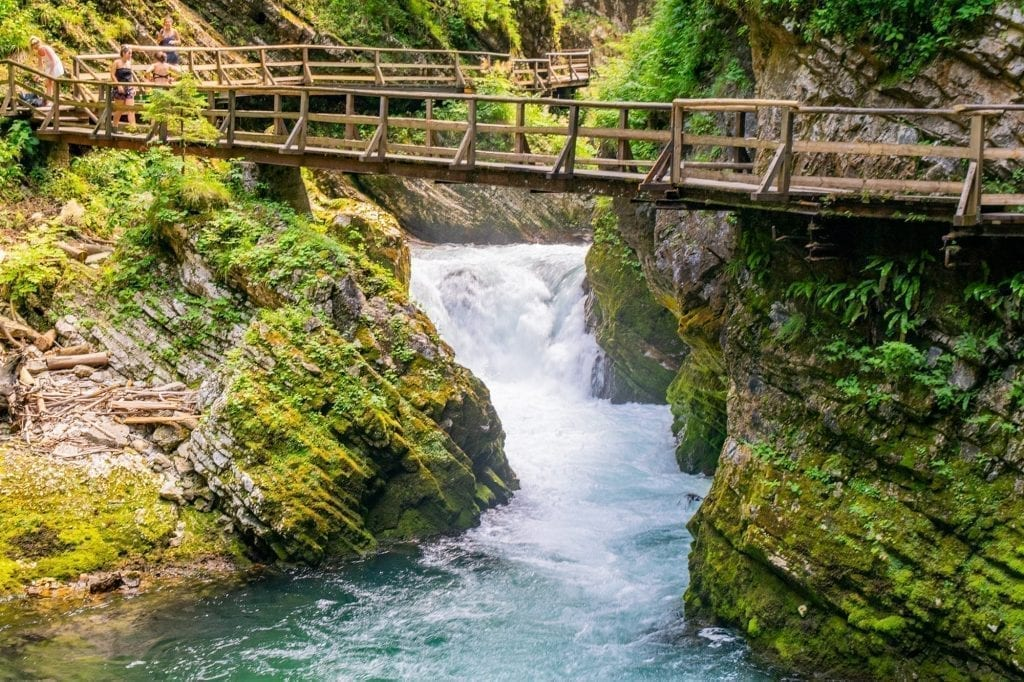 Photo of the Vintgar Gorge waterfall with a wooden boardwalks across it. Vintgar Gorge is one of the best day trips from Ljubljana Slovenia