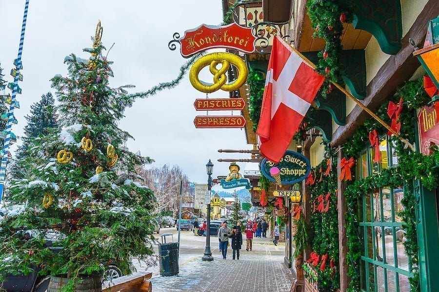 Small street in Leavenworth Washington decorated for Christmas, with a Christmas tree on the left side of the photo