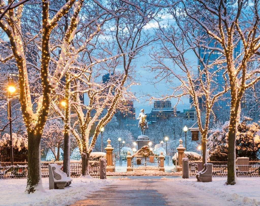 Commonwealth Avenue in Boston MA under a blanket of snow with Boston Public Garden visible in the background