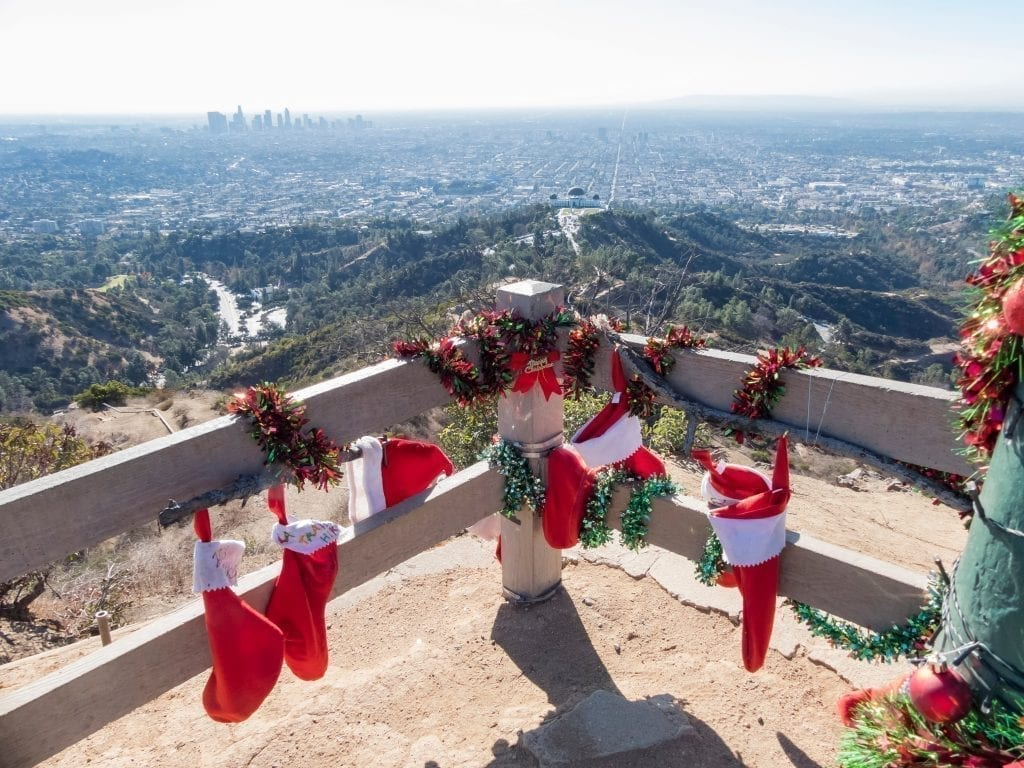 View of LA skyline from Griffith Park with stockings and holiday decor in the foreground--you can expect decor like this when visitin LA on a USA Christmas trip