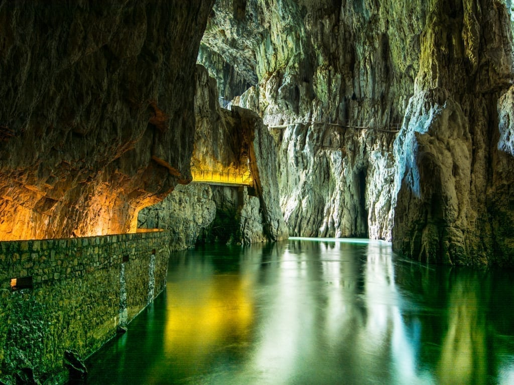 Underground river in Skocjan Cave in Slovenia, with a lit walkway visible on the left side of the photo