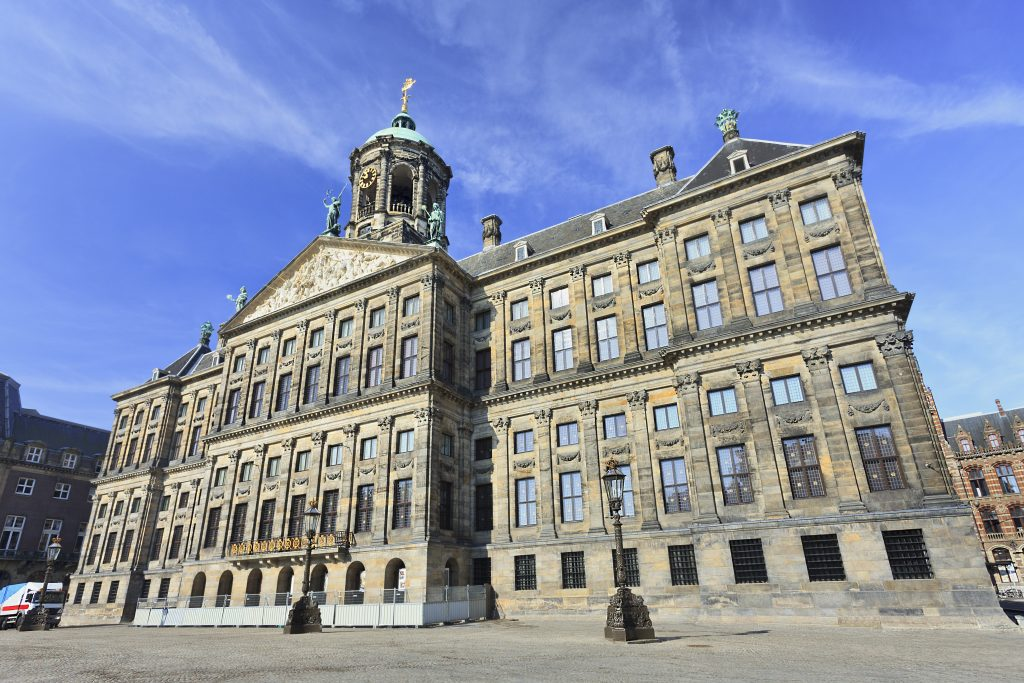 royal palace in dam square on a sunny day, a must see during a day in amsterdam the netherlands