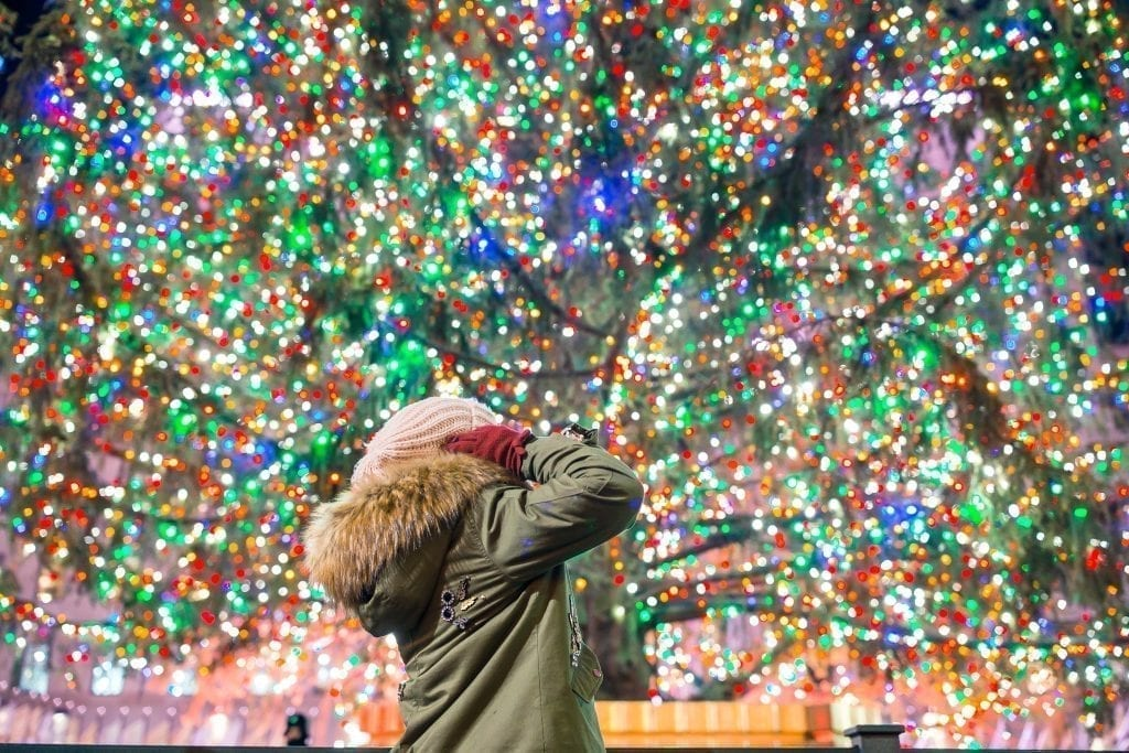 Woman in a green coat looking up at the Rockefeller Christmas tree with colorful lights. NYC is a classic Christmas vacation usa