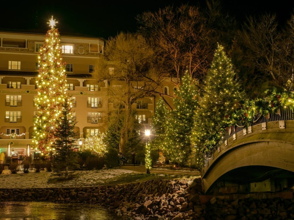 Colorado Springs decorated for the holidays with multiple Christmas trees, as seen at night