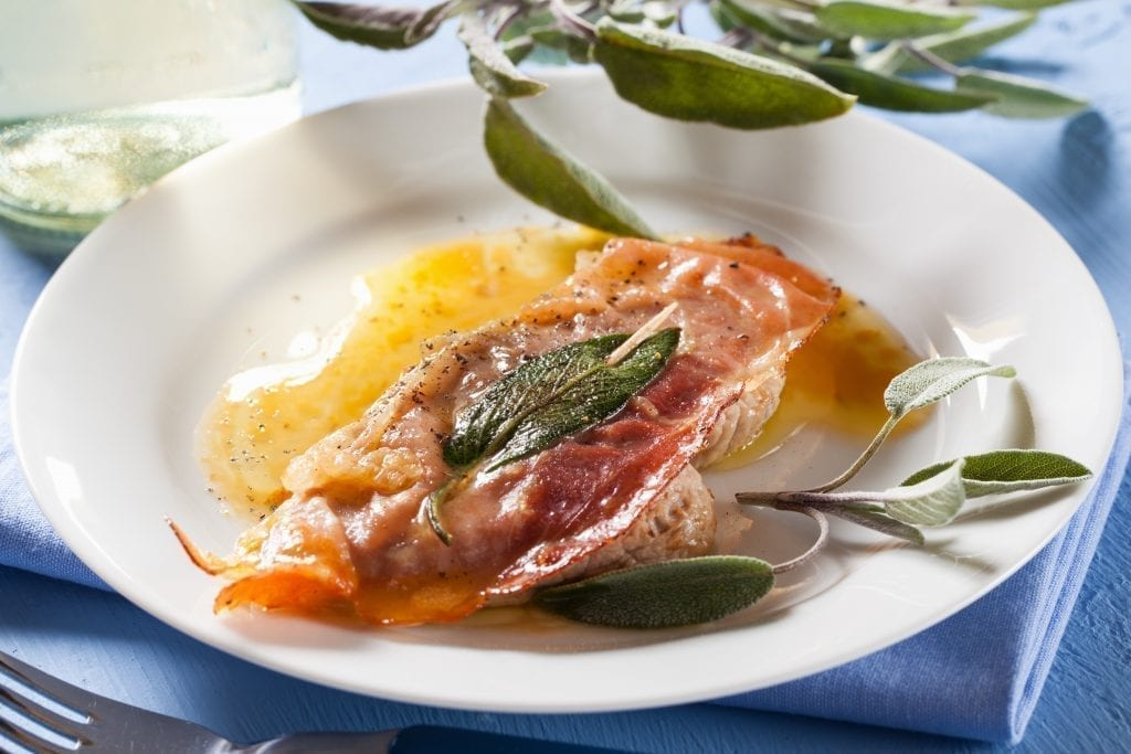 Saltimbocca on a white plate with bay leaves in the background
