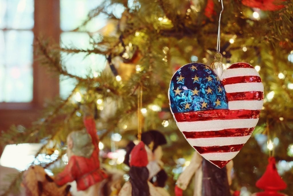 Heart-shaped Christmas ornament with an American flag painted on it hanging from a tree. This post rounds up the best christmas vacations in us