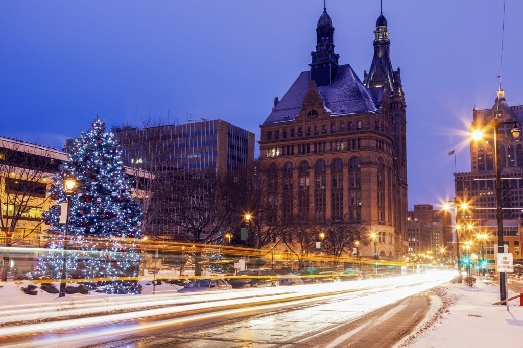 Long exposure of a street scene in Milwaukee at blue hour during the Christmas season, a Christmas tree is visible in the left side of the photo