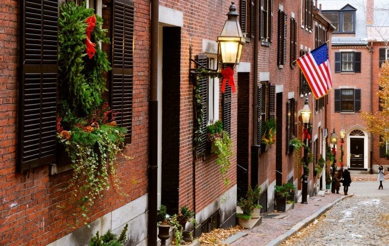 Acorn Street in Boston MA with Christmas decor hanging from the buildings on the left and an American flag in the distances. Boston is one of the best Christmas vacations in us