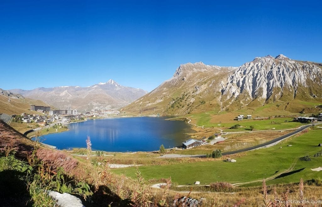 Village of Tignes France in the left of the photo, with most of the image including a mountain lakes and mountains on the right side of the photo. This image is of Tignes in summer.