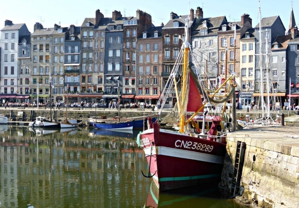 Harbor of Honfleur, one of the prettiest small towns in France. a small red boat is in the foreground and a line of buildings in the background