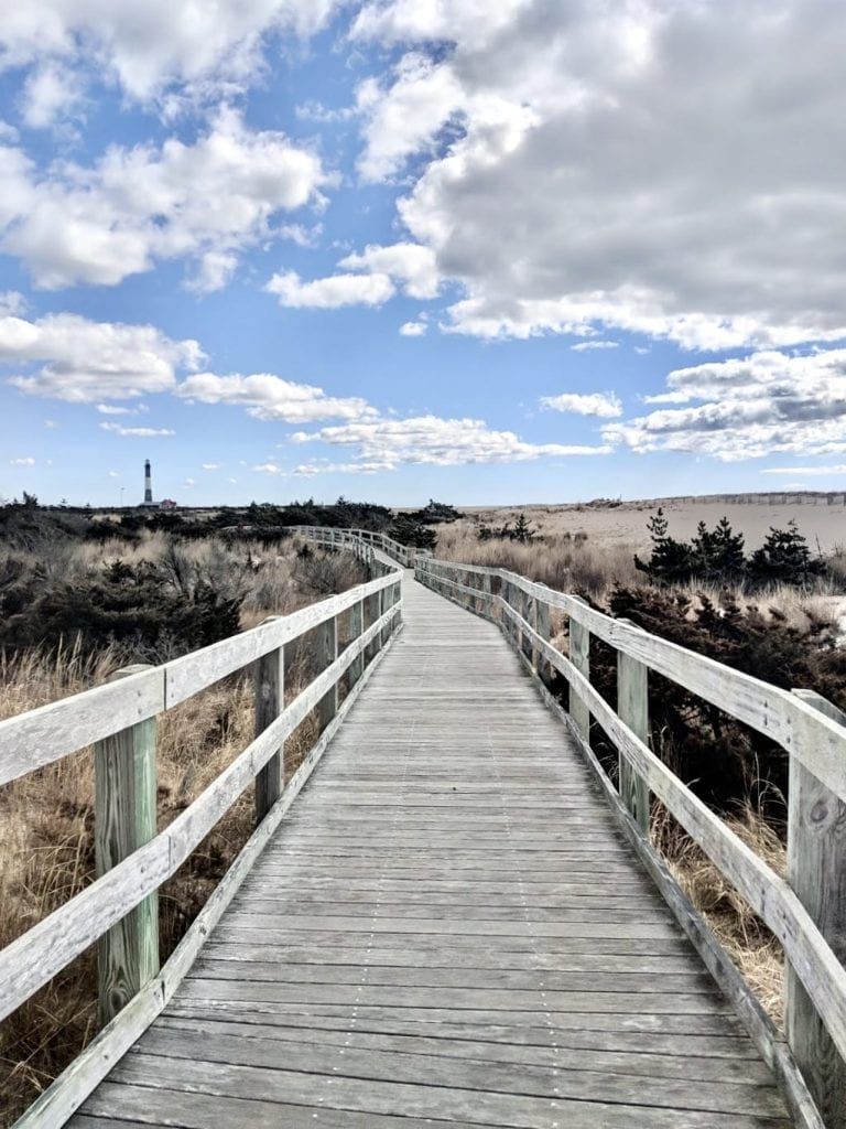 Long stretch of aged wooden boardwalk on Fire Island National Seashore under a partly cloudy sky