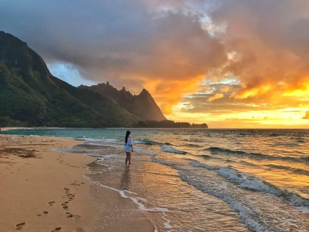 Tunnels Beach on Kauai at sunset, a woman is visible in the background