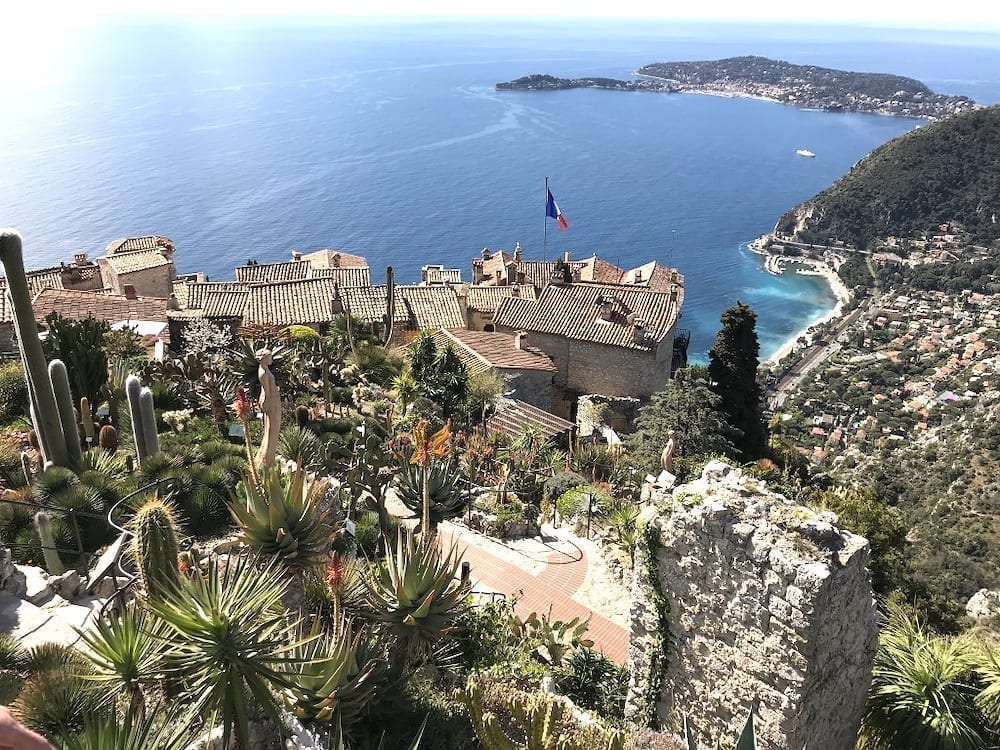 View of Eze from above, with a French flag visible above the village and the Mediterranean Sea in the background. Eze is one of the best small towns in France.