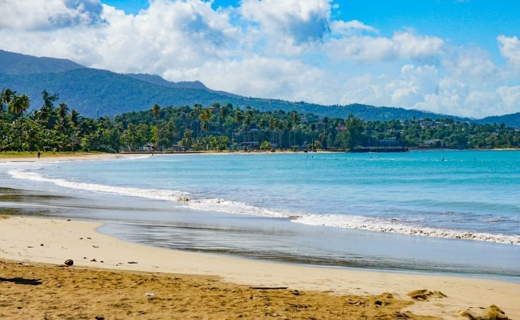 Luquillo Beach in Puerto Rica with a blue sky above it and golden sand in the foreground