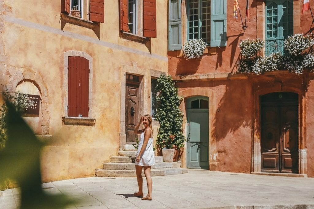 Photo of a blonde woman in a white dress standing in front of colorful red and yellow buildings in Roussillon
