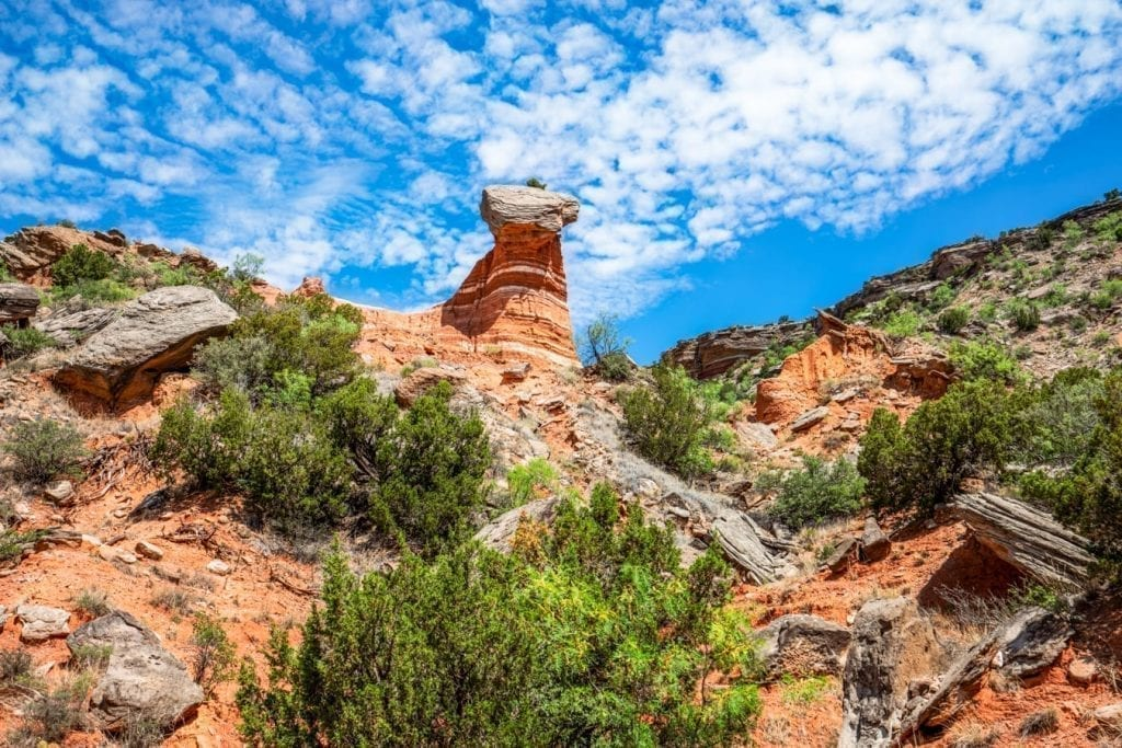 Hoodoo in Palo Duro Canyon Texas under a bright blue, partly cloudy sky