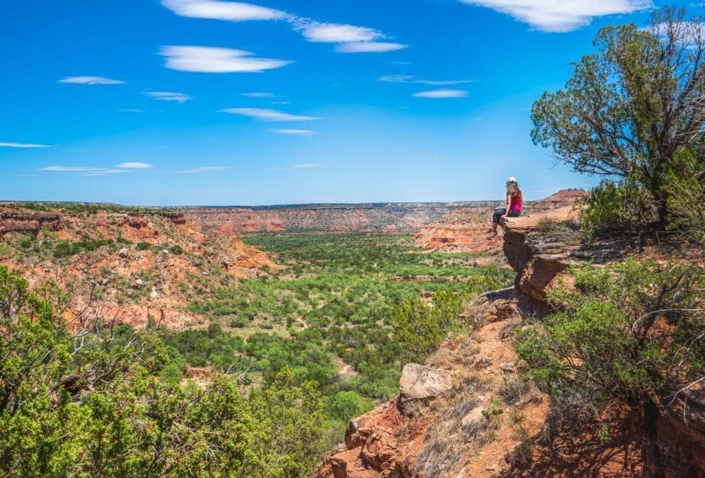 Kate Storm perched on the ledge of Palo Duro Canyon overlooking the green canyon below