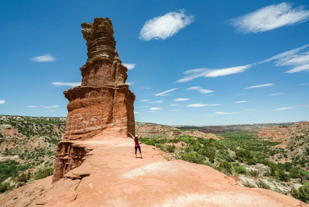 Kate Storm standing with her back to the camera in front of the Lighthouse in Palo Duro Canyon Texas
